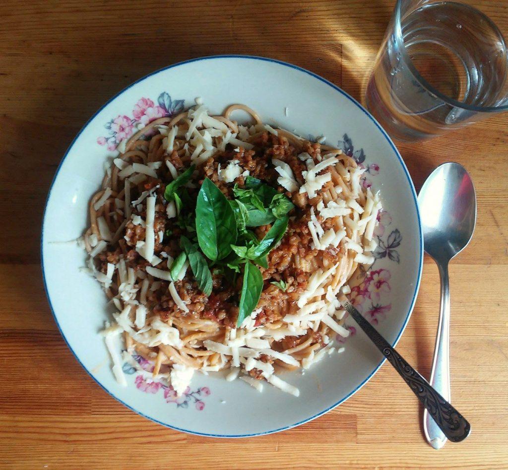 Spaghetti razowe z wegetariańskim bolognese (sos pomidorowy, podsmażona dobrze przyprawiona kasza gryczana) serem żółtym i świeżą bazylią. Woda